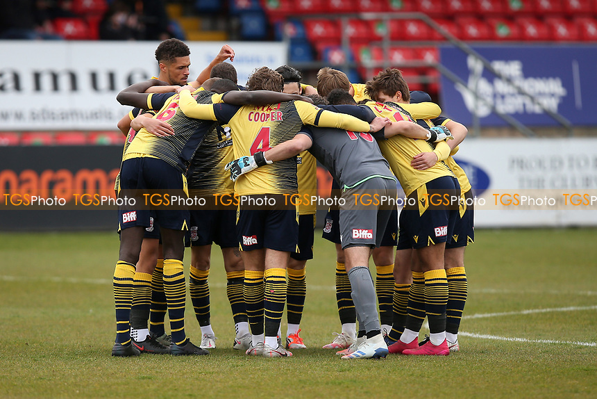 Woking players huddle during Dagenham & Redbridge vs Woking, Vanarama National League Football at the Chigwell Construction Stadium on 3rd May 2021