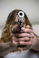 Caucasian blonde woman pointing handgun