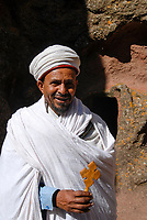 ETHIOPIA, Amhara region, Lalibela , monolith rock churches built by King Lalibela 800 years ago, St. Georg church, orthodox priest of Bet Giyorgis with wooden cross / AETHIOPIEN Lalibela oder Roha, Koenig LALIBELI liess die monolithischen Felsenkirchen vor ueber 800 Jahren in die Basaltlava auf 2600 Meter Hoehe hauen und baute ein zweites Jerusalem nach, orthodoxer Priester der Georgskirche mit Holzkreuz, Bet Giyorgis