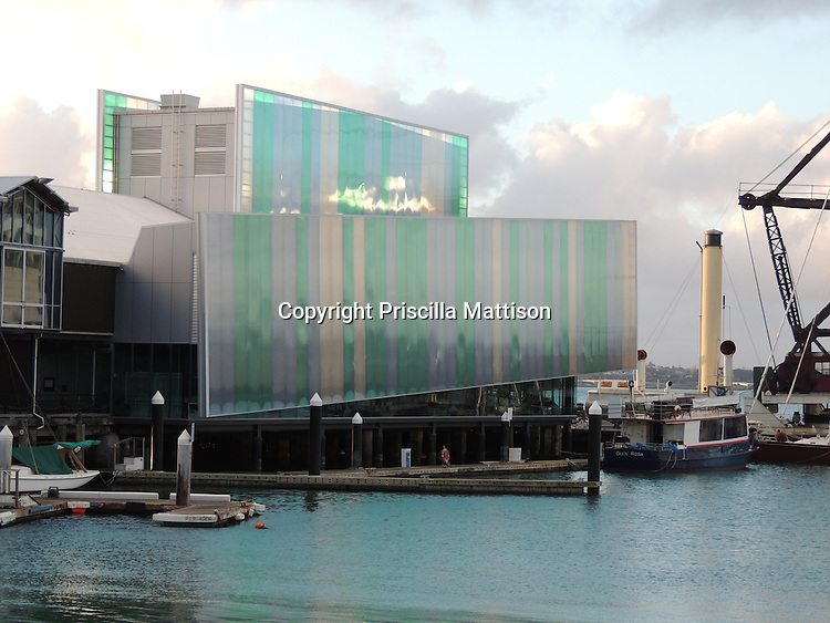 Auckland, New Zealand - September 17, 2012:  Harbor activity surrounds the pastel facade of the Voyager New Zealand Maritime Museum.