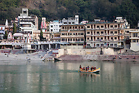 India, Rishikesh.  Rafting on the Ganges (Ganga). Temples and Guest Houses in the background.