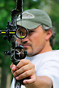 T35M:00105-048.04 Bowhunting:  Archer is at full draw and aiming at camera.  Bowsight, bubble, Whisker biscuit.