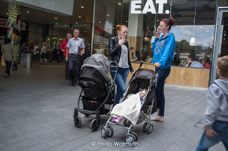 Two young mothers with pushchairs, Stratford, London.
