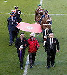Members of the armed forces and veterans carry the poppy from the playing field