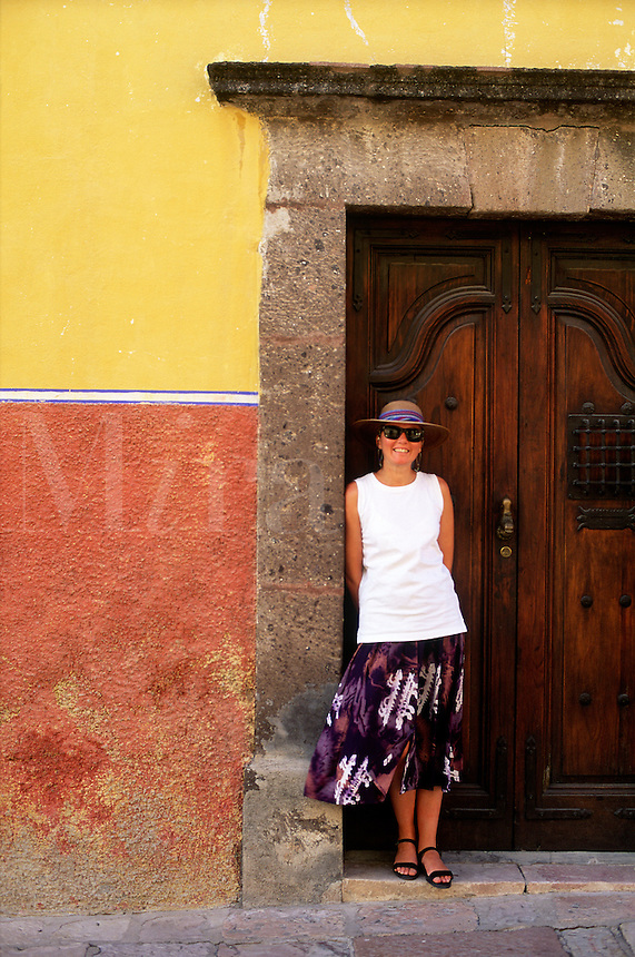 Female tourist posing in front of a building facade, Mexico