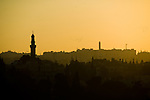 Setting sun turned the sky yellow and orange, silhouetting mosque minarets and the city skyline on some of the seven hills in Amman, Jordan.  © Rick Collier