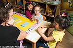 Education Preschool 4-5 year olds female teacher working with group of girls on game that involves turn taking