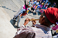 """A Salvadoran man plays flute during the procession of the Flower & Palm Festival in Panchimalco, El Salvador, 8 May 2011. On the first Sunday of May, the small town of Panchimalco, lying close to San Salvador, celebrates its two patron saints with a spectacular festivity, known as """"Fiesta de las Flores y Palmas"""". The origin of this event comes from pre-Columbian Maya culture and used to commemorate the start of the rainy season. Women strip the palm branches and skewer flower blooms on them to create large colorful decoration. In the afternoon procession, lead by a male dance group performing a religious dance-drama inspired by the Spanish Reconquest, large altars adorned with flowers are slowly carried by women, dressed in typical costumes, through the steep streets of the town."""