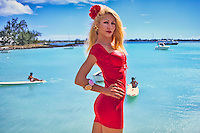 Beautiful young blond woman in red dress posing on tropical island