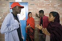 Djibouti. Djibouti province. Djibouti. Centre de santé communautaire d'Enguela (CDC). Health center. Behavioural Change Communication (BCC). Samia Abdillah Assoweh ( on the right with a brown veil on her head) is a black muslim young woman, She works as a psychosocial consellor on the VIH Aids disease. HIV Aids sensibilisation to young men and a woman. The Global Fund through the djiboutian Ministry of Health supports the programm with an Aids grant (financial aid).  © 2006 Didier Ruef