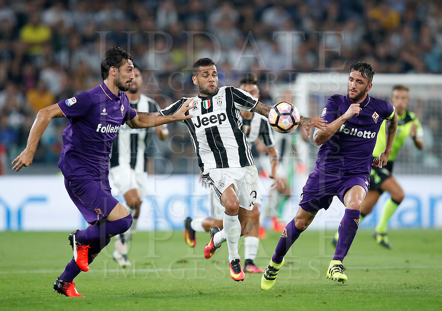 Calcio, Serie A: Juventus vs Fiorentina. Torino, Juventus Stadium, 20 agosto 2016.<br /> Juventus' Dani Alves, center, is challenged by Fiorentina's Davide Astori, left, and Gonzalo Rodriguez, during the Italian Serie A football match between Juventus and Fiorentina at Turin's Juventus Stadium, 20 August 2016. Juventus won 2-1.<br /> UPDATE IMAGES PRESS/Isabella Bonotto