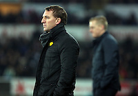 SWANSEA, WALES - MARCH 16: Liverpool manager Brendan Rodgers (L) and Swansea manager Garry Monk watch the game from the dugout during the Premier League match between Swansea City and Liverpool at the Liberty Stadium on March 16, 2015 in Swansea, Wales