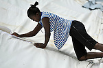 Marie Yolande Saint Felix, a field worker for the Lutheran World Federation, helps assemble a large tent being erected for use as a school classroom in the remote Haitian village of Embouchure. The village's school, run by the Episcopal Church, was damaged in the January 12, 2010, earthquake, but classes have continued to take place in the damaged structure. Villagers are now tearing down the old school to build a new one, and will use the tent classroom during the construction period. The school construction in Embouchure is funded by International Orthodox Christian Charities and FinnChurch Aid.