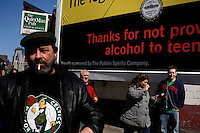 "People walk past a public service sign in South Boston, Massachusetts, that states ""The City of Boston reminds you: The legal drinking age is 21,"" on the day of the St. Patrick's Day Parade."