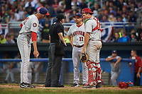 Auburn Doubledays manager Jerad Head (11) argues a play at the plate with umpire Drew Saluga as catcher Nic Perkins (43) watches relief pitcher Gabe Klobosits (31) point to the spot the runner slid in during a game against the Batavia Muckdogs on July 4, 2017 at Dwyer Stadium in Batavia, New York.  Batavia defeated Auburn 3-2.  (Mike Janes/Four Seam Images)