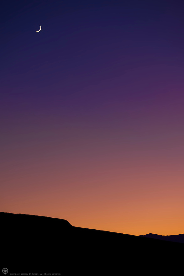 A sliver of moon sets over the desert sunset