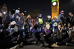 © Joel Goodman - 07973 332324 . 05/11/2016 . London , UK . Protesters sit in and block the road outside Parliament . Supporters of Anonymous , many wearing Guy Fawkes masks , attend the Million Mask March bonfire night demonstration , in central London . Photo credit : Joel Goodman