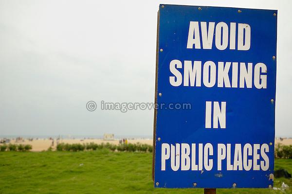 "India, Tamil Nadu, Chennai (Madras). Signpost reading ""Avoid smoking in public places"" on Chennai beach."