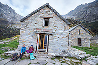 The Via Alta Verzasca is a five day ridge traverse hike above the Valle Verzasca in the Ticino region of Switzerland. Hikers at the Capanna Cognora in the early morning getting ready to hike the last day.