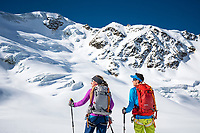 The Ortler Group in northern Italy is a popular region for spring ski touring using the huts for overnights to ski all the many peaks in the mountain group. Two ski tourers stopped on the glacier below the Punta San Matteo.