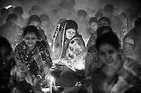 A Hindu woman lights a candle   ( named locally as Prodip ) for a special prayer during the Kartik Brati or Rakher Upobash religious festival in Barodi,  Near Dhaka, Bangladesh