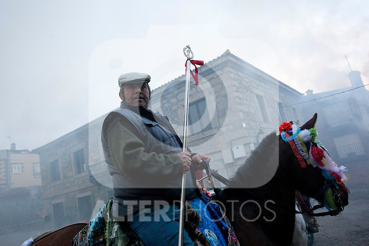SAN BARTOLOME DE PINARES, SPAIN - JANUARY 17: The Mayordomo traverses the streets of the village riding his horse while people go out of their houses for kissing San Anton¥s image on January 17, 2013 in San Bartolome de Pinares, Spain. In honor of San Anton, the patron saint of animals, horses are riden through the bonfires on the night before the official day of honoring animals in Spain. Victor J. Blanco / Alterphotos