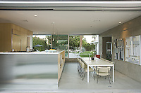 Diningroom and kitchen seen from outside through open movable aluminum walls in mid-century home
