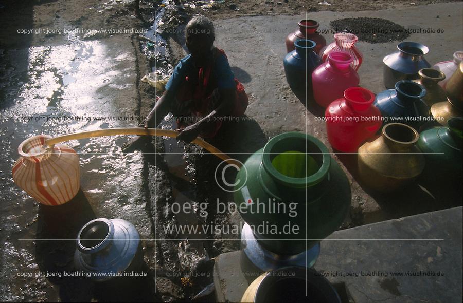 INDIA, Tamil Nadu, woman fills pots with drinking water from a tap which runs onetime a day only in a fishing village near Nagapattinam / INDIEN Frau füllt Trinkwasser in Krüge von einem Wasserhahn ab