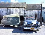 1950 blue Studebaker parked next to a 1956 green Kom-Pak Sportsman trailorboat.