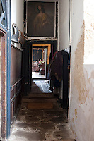 This dilapidated but charming corridor still bares the signs of a once rich facade, its panelled walls, and display of armour now peeling and rusting