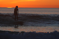Pacific Beach, San Diego, California, USA:  Monday, January 19 2009.  The sun sets behind a surfer riding her board along the shore at the bottom of Loring Street.  The Martin Luther King Jnr Day holiday was marked by warm weather, big surf and a technicolored sunset as much of the rest of the country shivered in the cold.