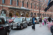 Black cab taxis queue for passengers at St Pancras station London