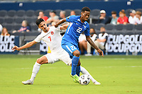 KANSASCITY, KS - JULY 11: Romario Barthelery #22 of Martinique holds off Stephen Eustaquio #7 of Canada during a game between Canada and Martinique at Children's Mercy Park on July 11, 2021 in KansasCity, Kansas.