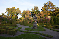 The clipped hedges and lilac trees in the formal parterre are bathed in soft evening light