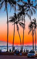 Locals and tourists watch the sun set past Ka'ena Point from Hale'iwa Beach Park, O'ahu.