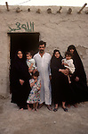 Marsh Arabs. Southern Iraq. Marsh Arab man and three wives and children outside their adobe home banks of river Tigris. Polygamous family group community. 1984