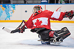 Sochi, RUSSIA - Mar 15 2014 - Corbin Watson has a shot go wide on him as Canada takes on Norway in the Bronze Medal Sledge Hockey game at Canada Paralympic House at the 2014 Paralympic Winter Games in Sochi, Russia.  (Photo: Matthew Murnaghan/Canadian Paralympic Committee)