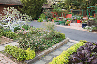 Rosalind Creasy front yard garden with driveway separating mixed beds of edible plants
