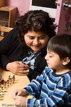 Education Preschool 3-4 year olds female teacher working with boy playing with small plastic figures talking vertical