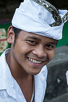 Bali, Indonesia. Young Hindu Man Wearing an Udeng, the Traditional Balinese Male Head Wrap.  Pura Dalem Temple.  Dlod Blungbang Village.