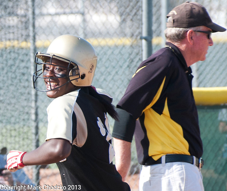 Softball player is all smiles after hitting a homerun.