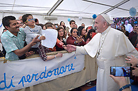 Pope Francis blesses a baby as worshipers greet him upon his arrival for a pastoral visit to the San Giulio parish on April 7, 2019 in Rome.