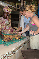 Two Peace Corps Volunteers and Senegalese Woman  Examining Roasted Peanuts, Fatick, Senegal
