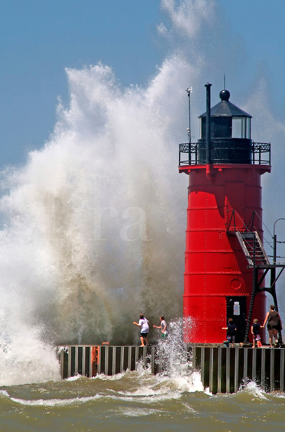 People on jetty watch large breaking waves in South Haven Michigan