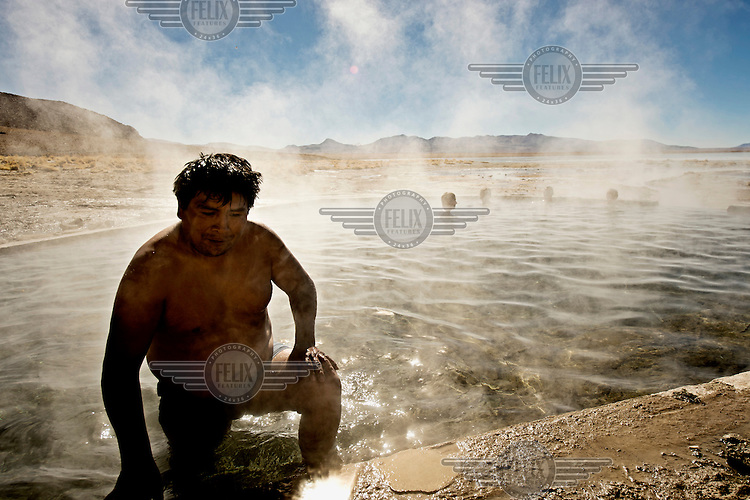 A man exits a natural hot spring at the Sol de Manana geysers, a geothermal field at a height of 5000 metres.
