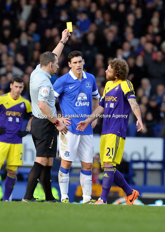 Pictured: Jose Canas of Swansea (R) sees a yellow card by match refereeKevin Friend (L).  Sunday 16 February 2014<br /> Re: FA Cup, Everton v Swansea City FC at Goodison Park, Liverpool, UK.