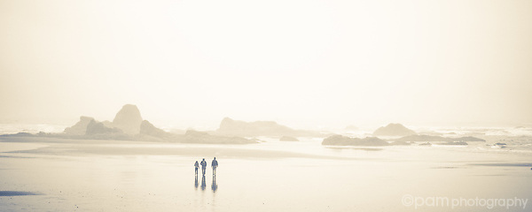 Panoramic of three young people walking on northern pacific beach in the fog.