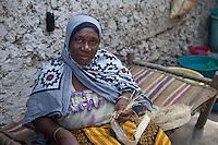 Jambiani, Zanzibar, Tanzania.  Woman Making a Strap by Braiding Grass.