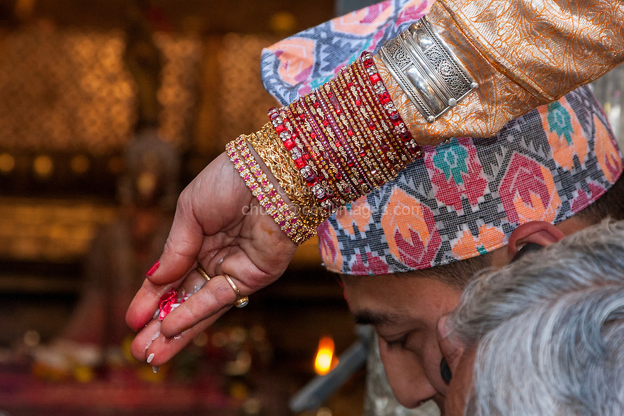 Nepal, Patan.  Bracelets on Bride's Arm as she Presents Offering of Rice and Flower Petals During Wedding Ceremony in the Golden Temple (Kwa Baha).