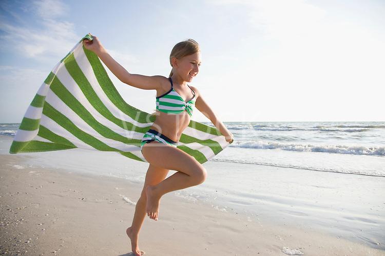 USA, Florida, St. Pete Beach, girl (8-9) running with towel on beach